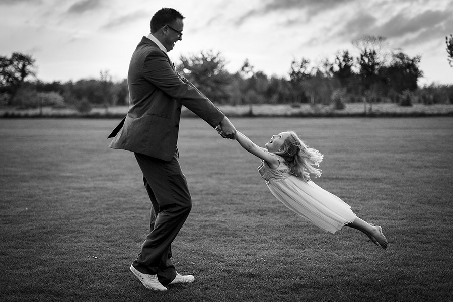 A girl is swung by her father at a wedding, joy, fun, play