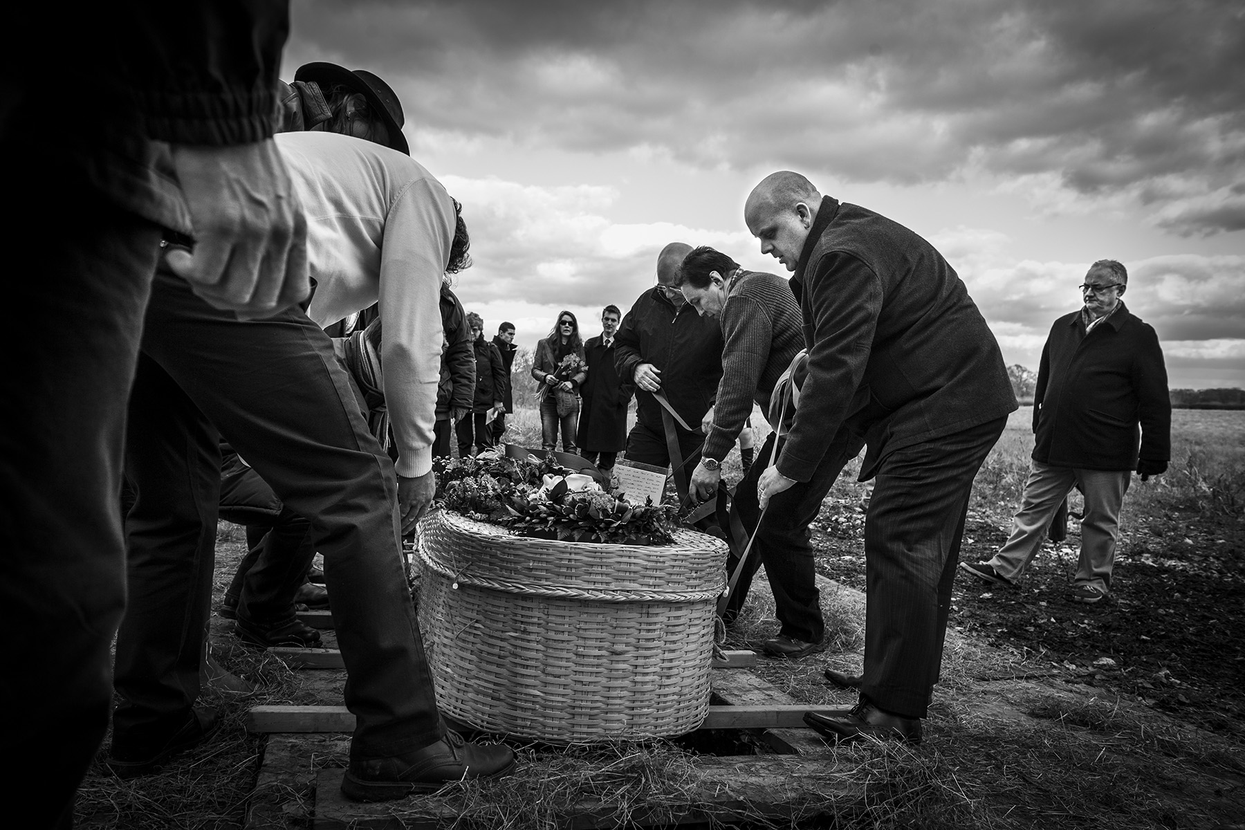 The commital, lowering Neil into the ground for his final resting place. Funeral, natural meadow burial.